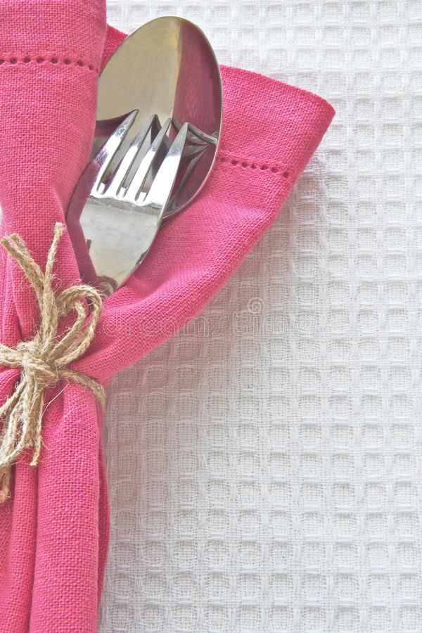 Spoon and Fork with pink serviette. On white linen cloth stock images