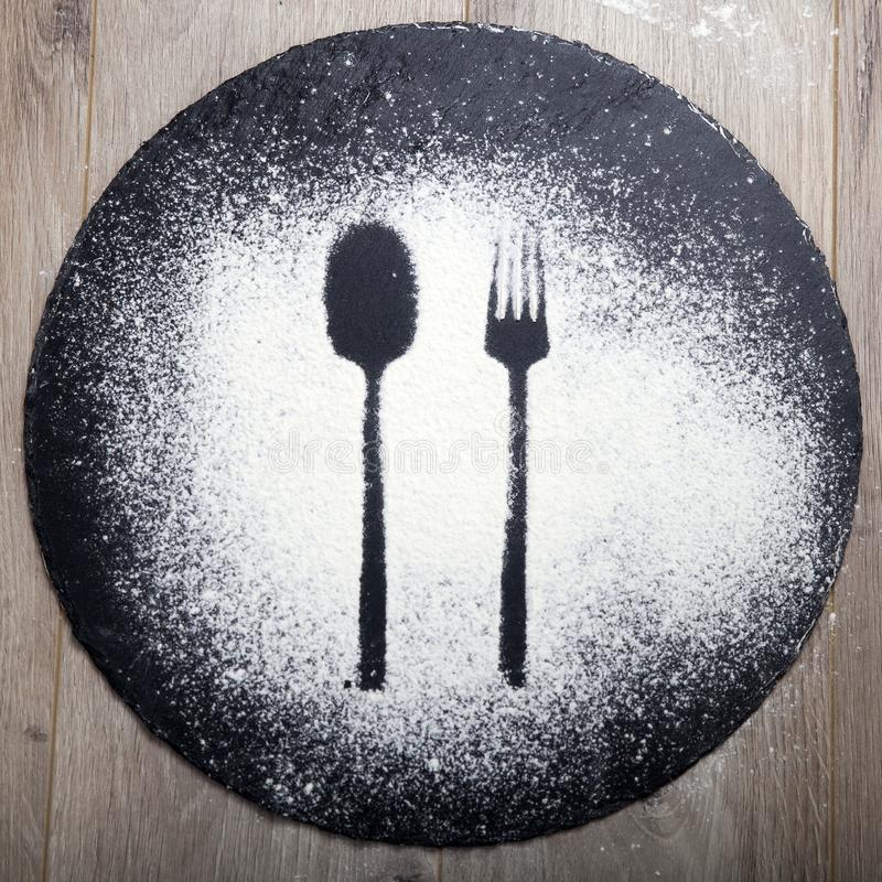 Spoon and fork silhouette made with flour on the dark texture background stock images