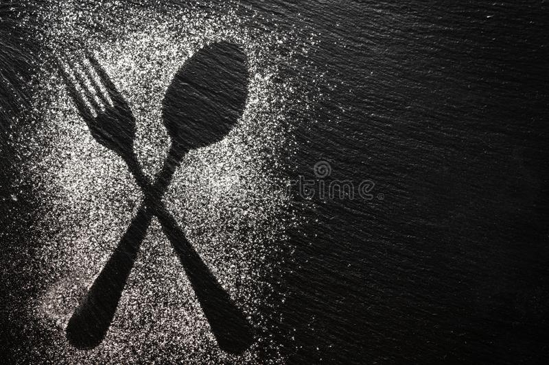 Spoon and fork silhouette made with flour on dark texture background, up horizontal view royalty free stock photography
