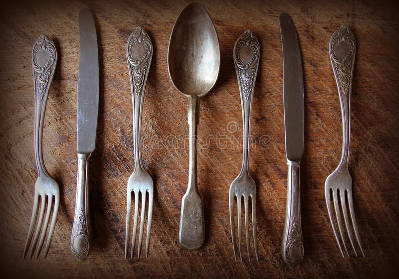 Spoon, forks, knives, ladles on a wooden table, selective focus and toned image. Top view stock photography
