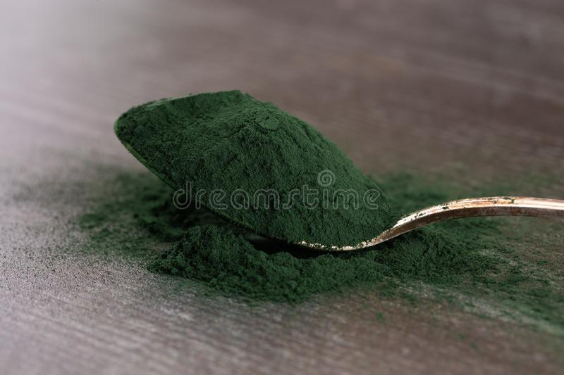 Spoon Full of Spirulina Powder on a Wooden Table. A Spoon Full of Spirulina Powder on a Wooden Table royalty free stock image