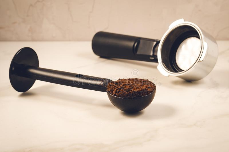 Spoon with ground coffee and holder/black spoon with ground coffee and holder, selective focus stock photos