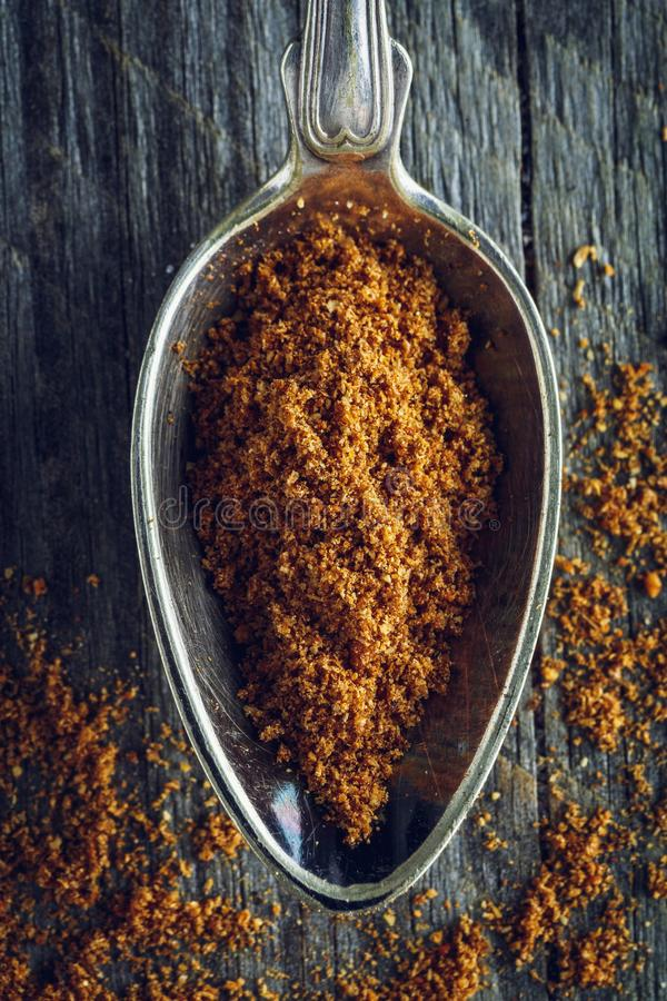 Spoon of ground nutmeg powder. On a wooden background. Macro shot stock images