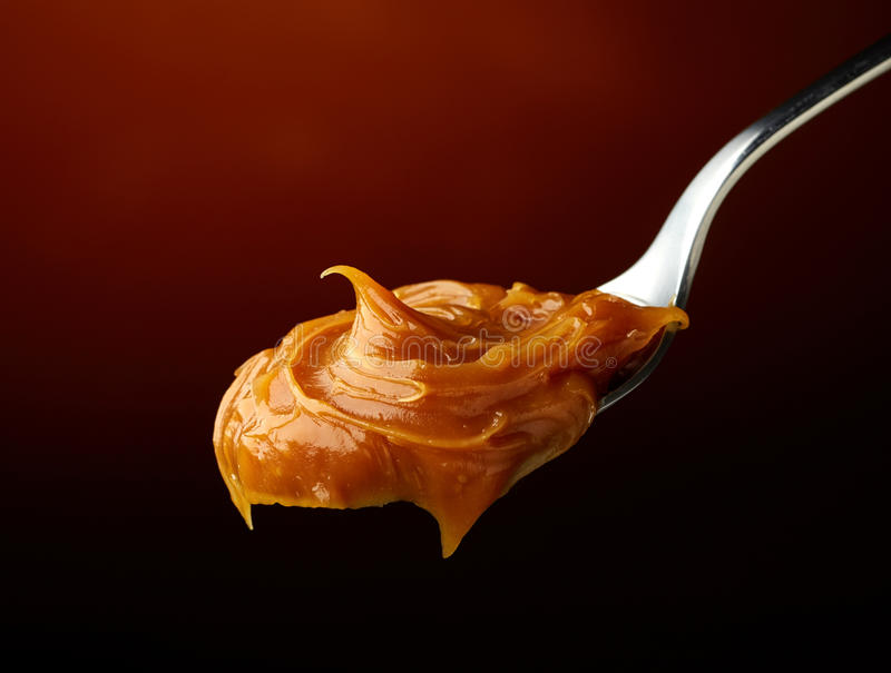 Spoon of melted caramel cream royalty free stock photography