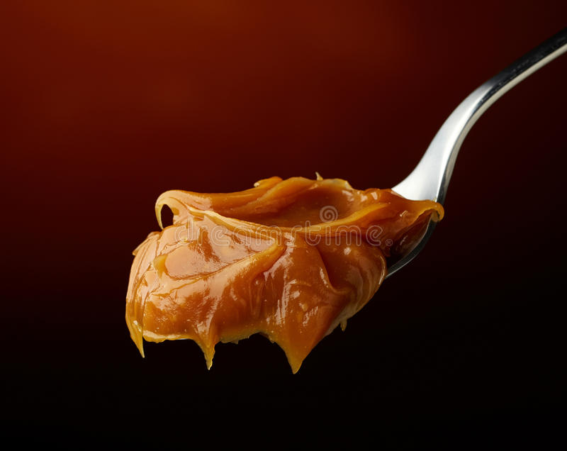 Spoon of melted caramel cream royalty free stock photos