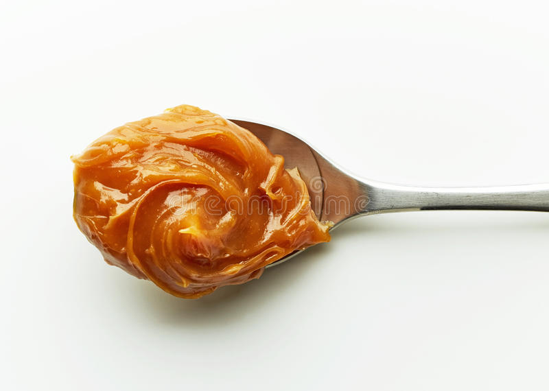 Spoon of melted caramel cream stock images