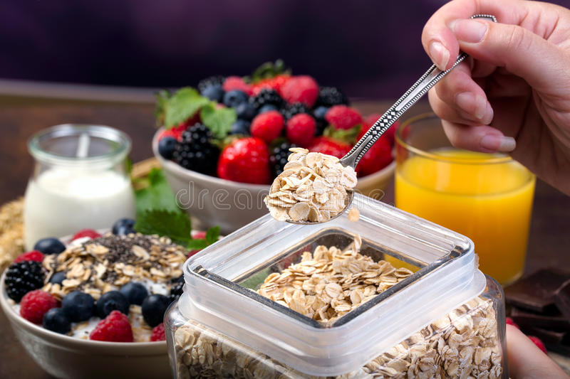 Spoon of oatmeal. Bowl with berries. stock photos