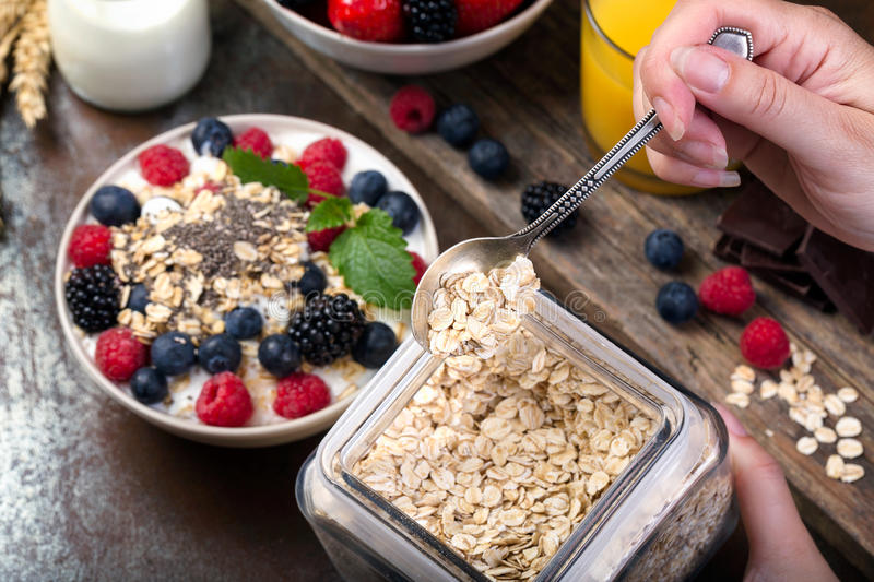 Spoon of oatmeal. Bowl with berries. royalty free stock photo