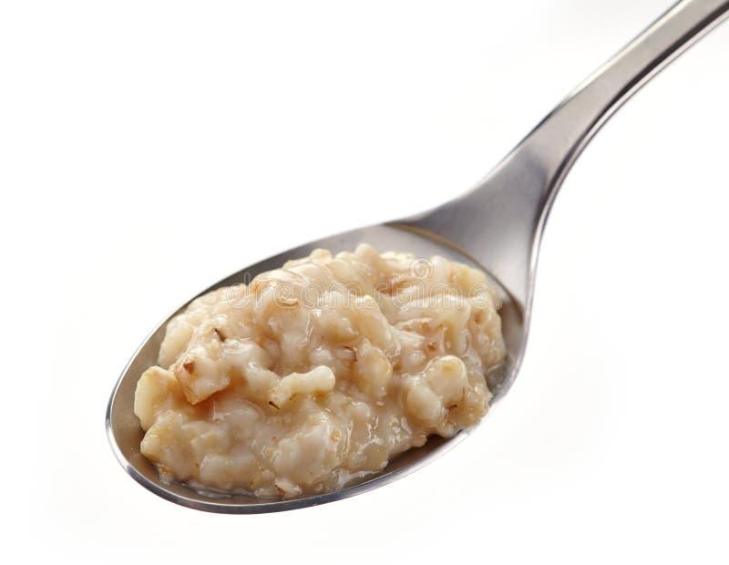 Spoon of oats porridge royalty free stock images