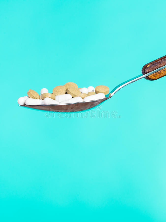 Spoon with pills on blue stock images