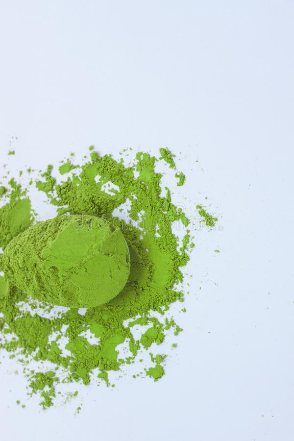 A spoon with powdered matcha green tea, isolated on light background, copy space, top view. Matcha green tea on light background. A spoon with traditional stock image