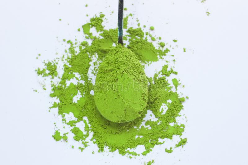 A spoon with powdered matcha green tea, isolated on light background, copy space, top view. Matcha green tea on light background. A spoon with traditional stock photo