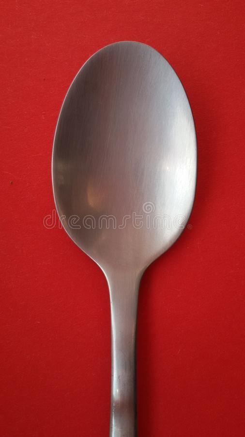 Spoon on red tablecloth or background. It is time for dinner. royalty free stock images