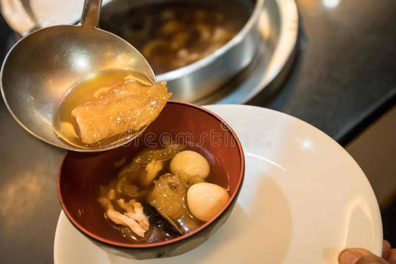 A spoon to scoop Chinese style soup; or braised fish maw in red gravy with eggs, mushroom, and bamboo shoot in white bowl. Braised Fish Maw in Red Gravy with stock photography