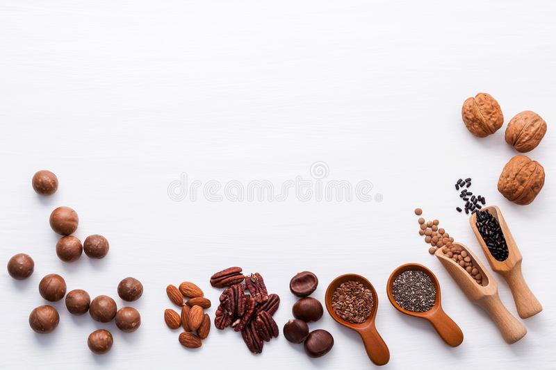 Spoon of various legumes and different kinds of nuts walnuts kernels ,hazelnuts, macadamia ,almond kernels,brown pinto. Red kidney beans and pecan set up on stock photography