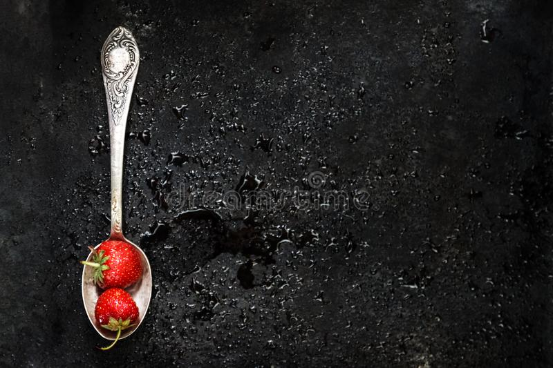 in a spoon a wet strawberry on a dark background with splashes o stock images