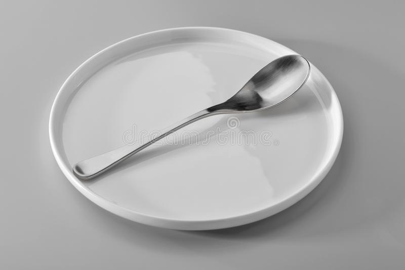 Spoon on white plate against neutral gray background royalty free stock photography