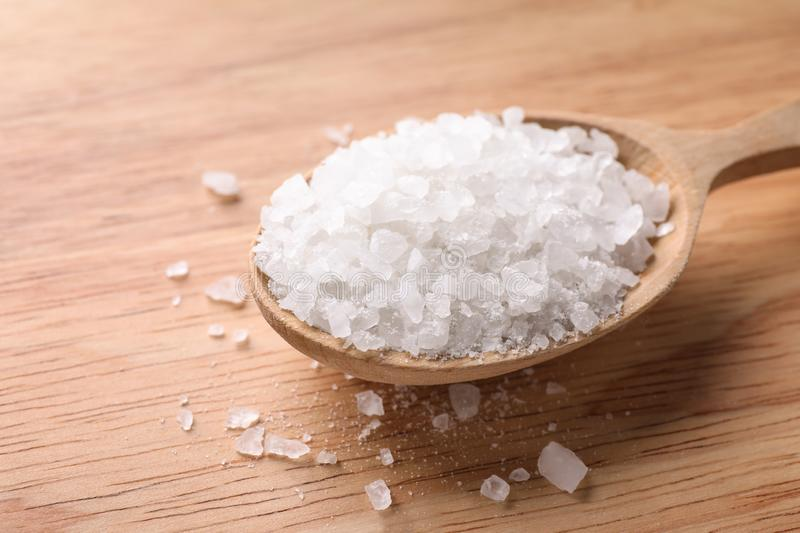 Spoon with white sea salt on wooden table. Spa treatment. Spoon with white sea salt on wooden table, closeup. Spa treatment stock image