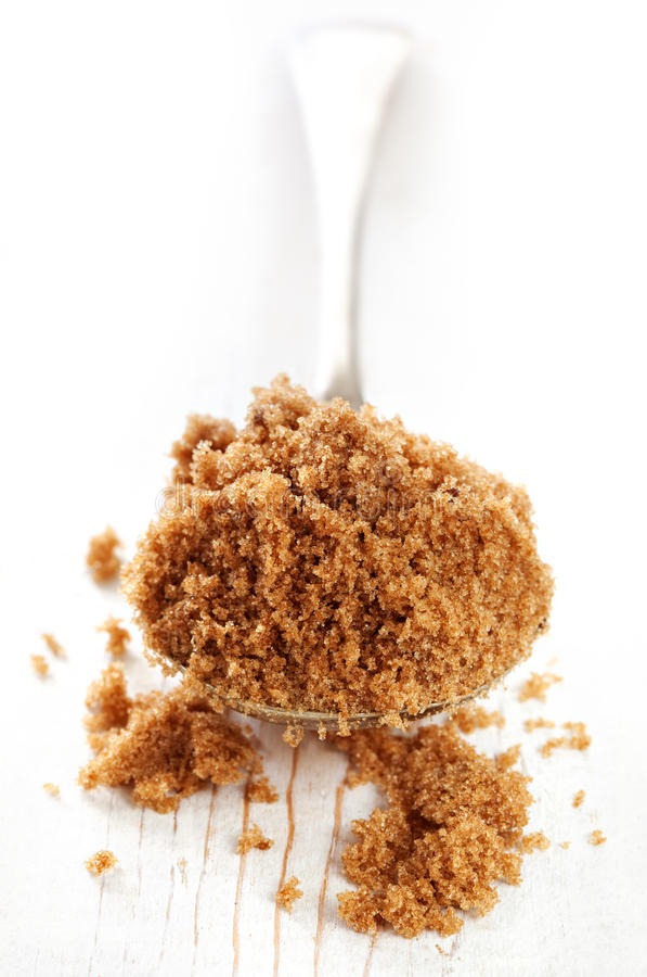 Spoonful of Brown Sugar. Spoonful of dark brown raw sugar, over rustic wood. Shallow depth of field stock image