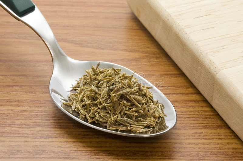 Spoonful of cumin seeds. A spoonful of cumin seeds besides a chopping board stock image