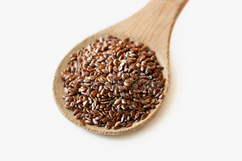 Spoonful of flax seeds isolated on white stock images