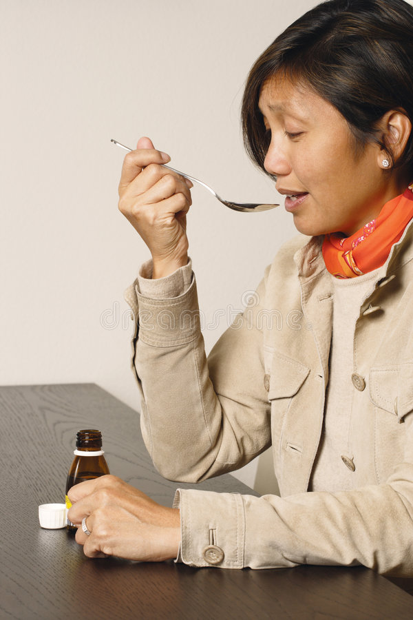 Spoonful of medicine. An Asian female in her early 40's taking a spoonful of cough medicine stock photos