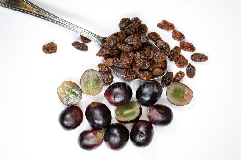 Spoonful of raisins. With red grapes on a white background stock image