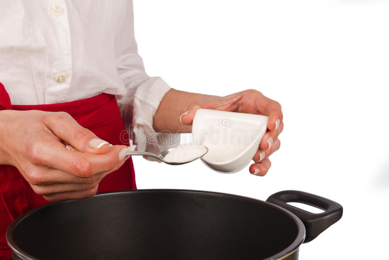 A spoonful of salt. Into a stewing pot royalty free stock photo