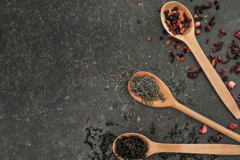 Spoons with different types of dry tea leaves on grey background royalty free stock photography