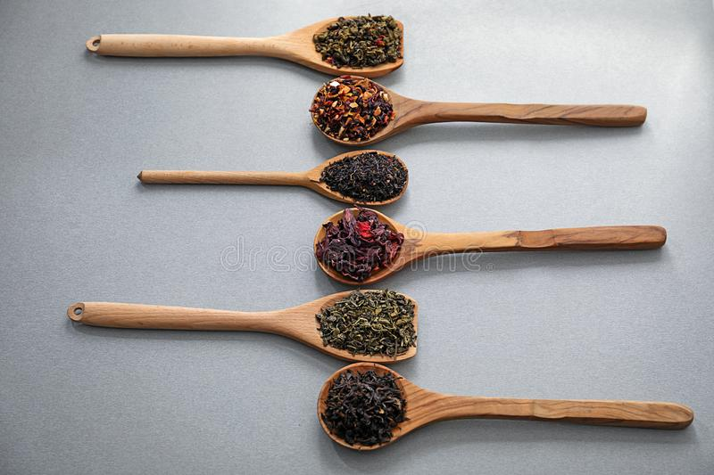 Spoons with different types of dry tea leaves on grey background royalty free stock photos