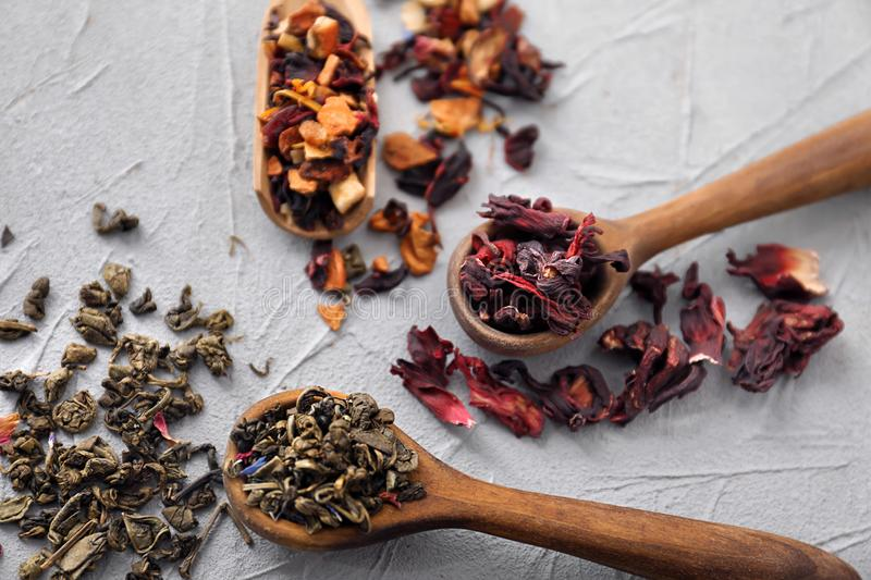 Spoons with different types of dry tea leaves on light background stock image