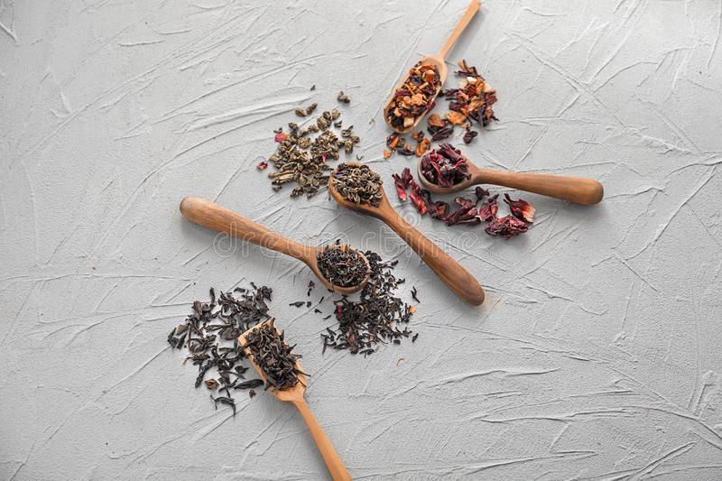 Spoons with different types of dry tea leaves on light background royalty free stock photo