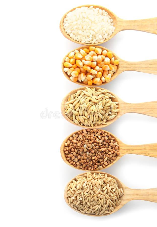 Spoons with different types of grains and cereals. On white background royalty free stock image