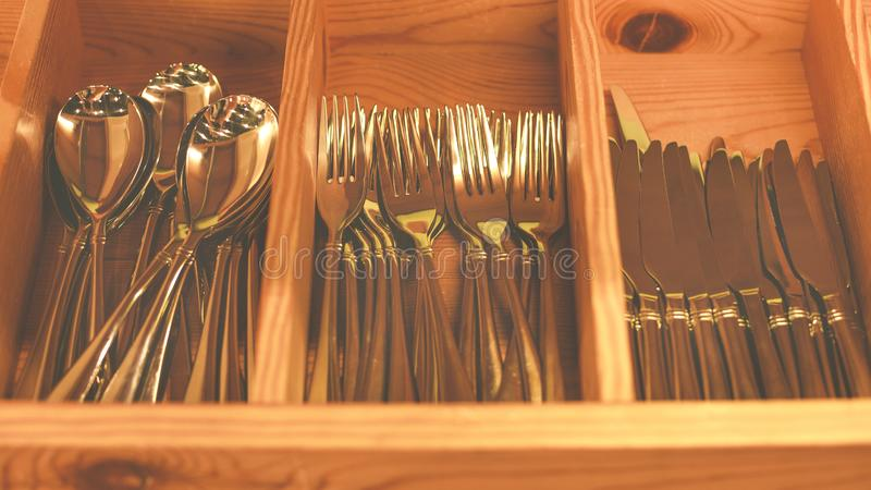 Spoons, forks, knives in the tray. Wooden drawer with modern cutlery. Kitchen or restaurant concept background. stock photography