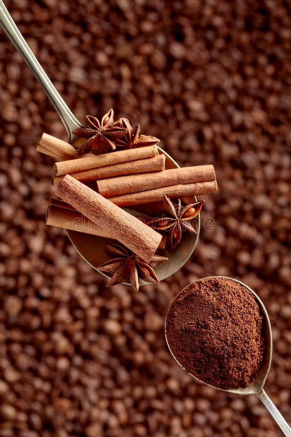 Spoons of ground coffee and anise with cinnamon sticks stock images