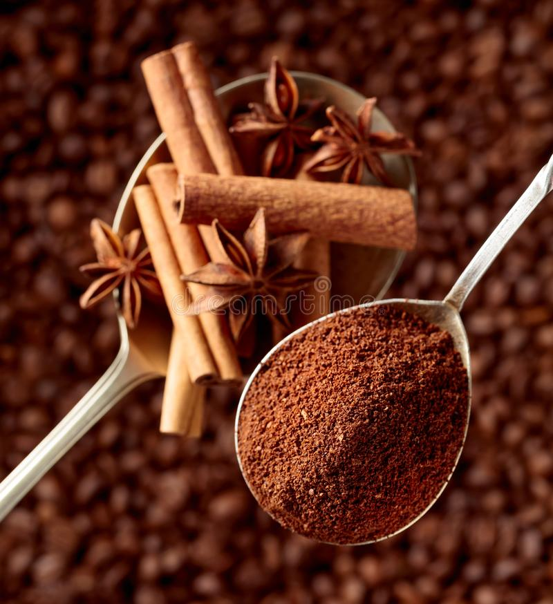 Spoons of ground coffee and anise with cinnamon sticks royalty free stock photography