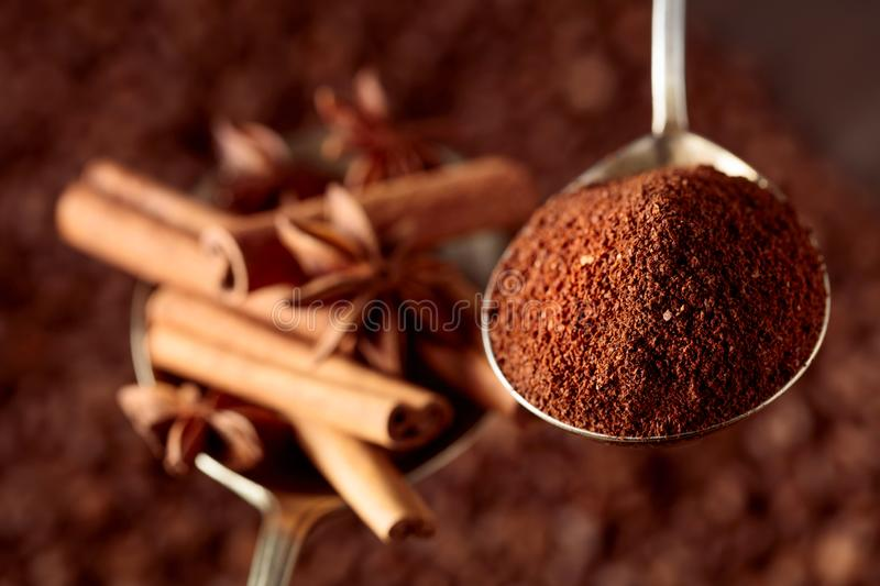 Spoons of ground coffee and anise with cinnamon sticks stock photos