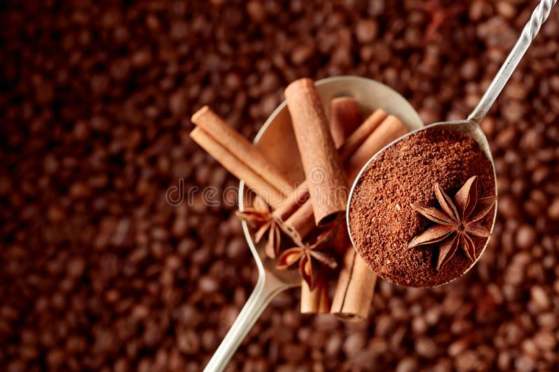 Spoons of ground coffee and anise with cinnamon sticks stock photo