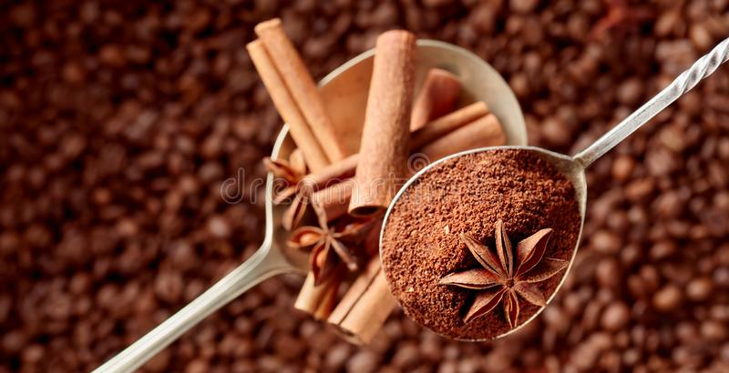 Spoons of ground coffee and anise with cinnamon sticks royalty free stock photos