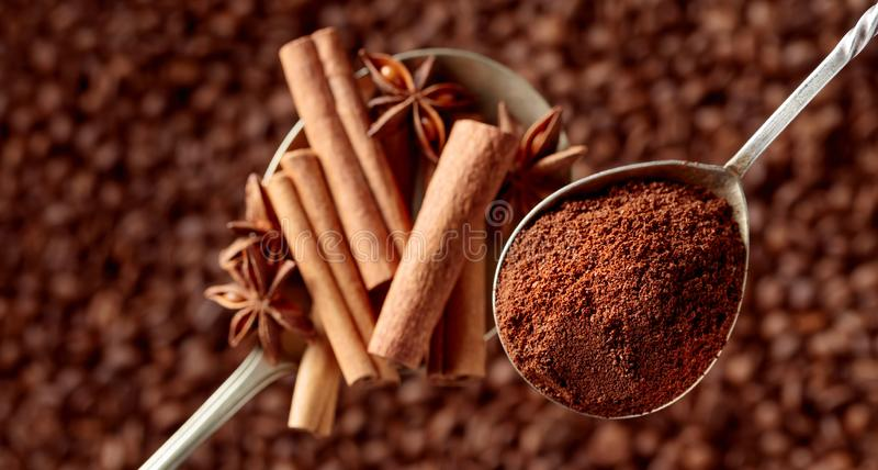 Spoons of ground coffee and anise with cinnamon sticks stock photography