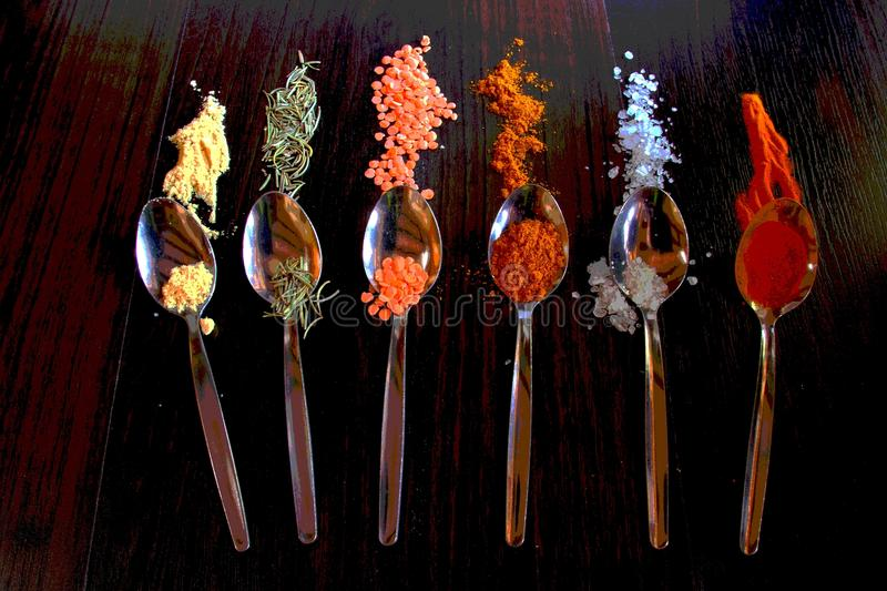 Spoons with spice on a dark surface. Spices erupt like mini volcanoes from spoons in explosions of flavor and taste