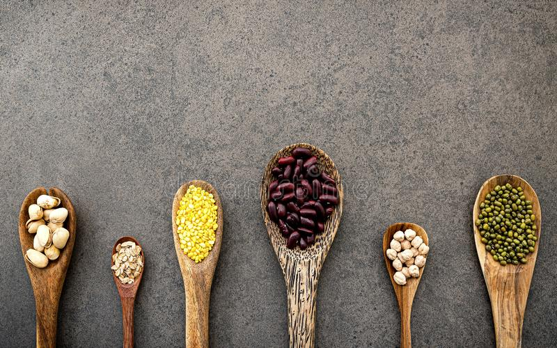Spoons of various legumes and beans set up on dark stone background royalty free stock photo