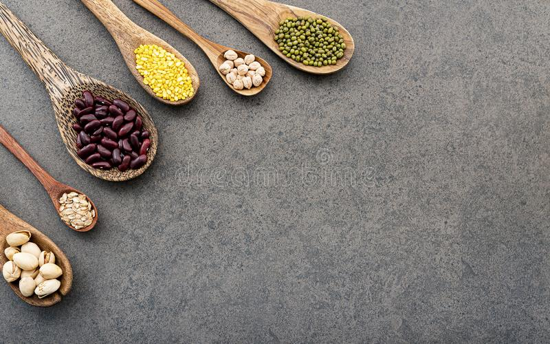 Spoons of various legumes and beans set up on dark stone background stock image