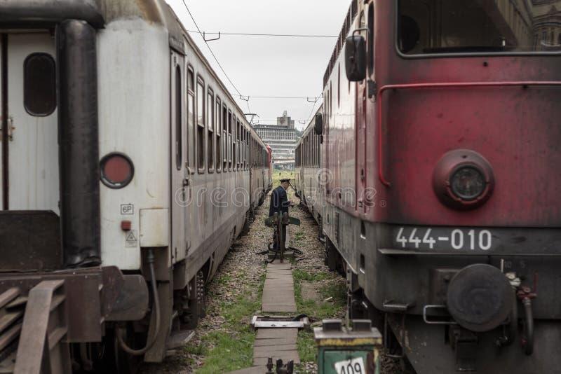 Spoorarbeider het manoevring tussen twee passagierstreinen op de platforms die van het station van Belgrado, hen maken voor vertr royalty-vrije stock afbeelding