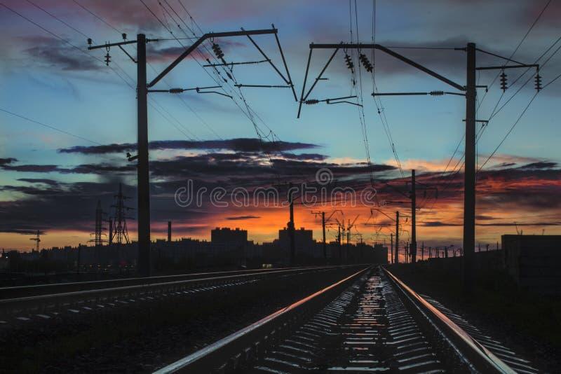 Spoorsporen die voor de stadszonsondergang weggaan stock foto