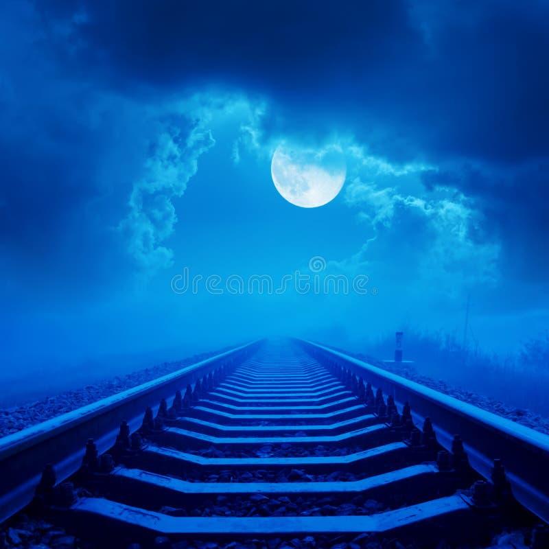 Spoorweg aan horizon in nacht met volle maan en wolken stock afbeeldingen
