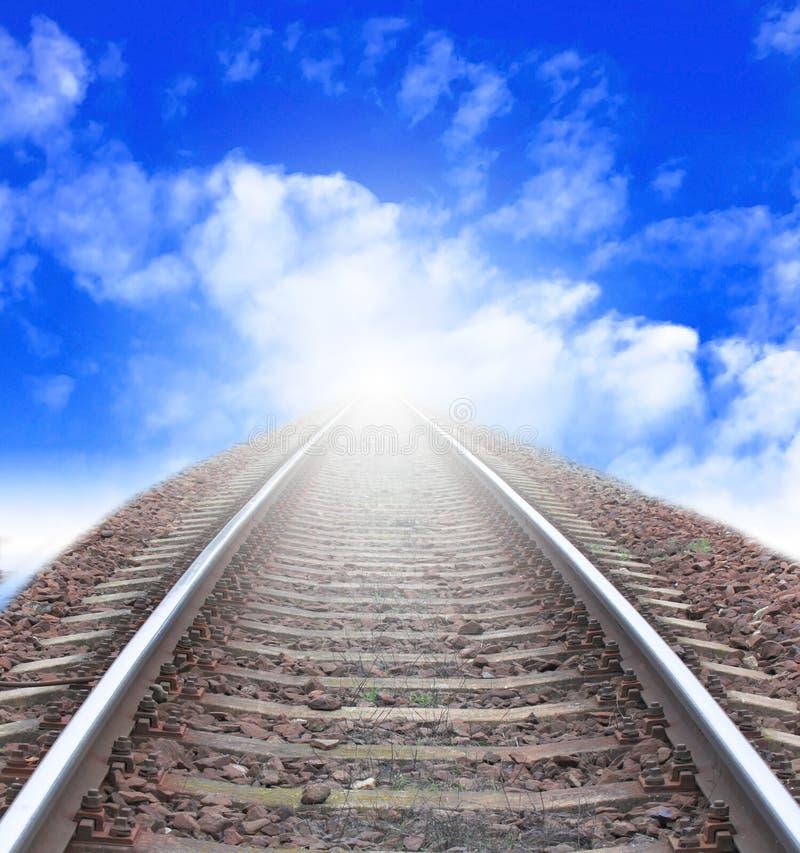 Spoorweg aan horizon onder bewolkte hemel met zon royalty-vrije stock afbeelding