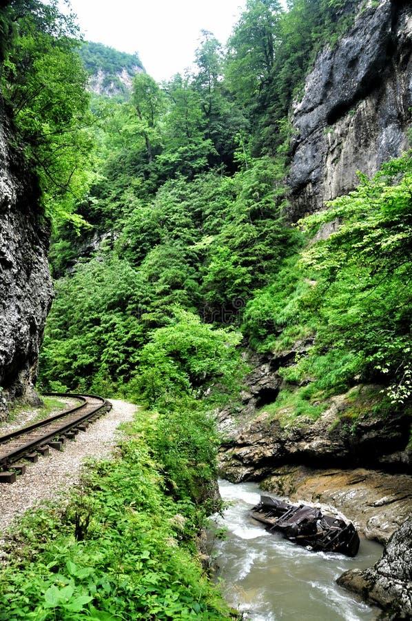 Spoorweg in de kloof van Guam op één kant van de rotsen, andere een diepe afgrond en kokende snelle rivier stock fotografie