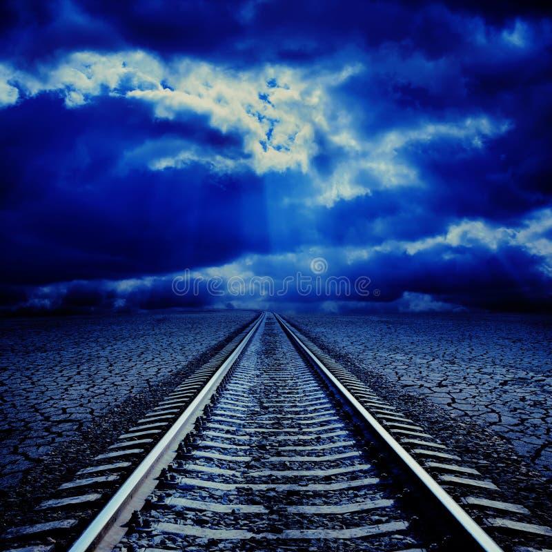 Spoorweg in nacht aan horizon stock fotografie