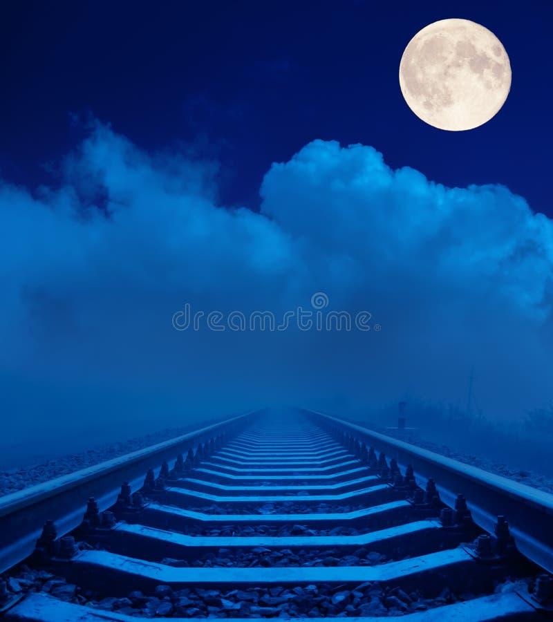 Spoorweg in nacht met volle maan stock fotografie